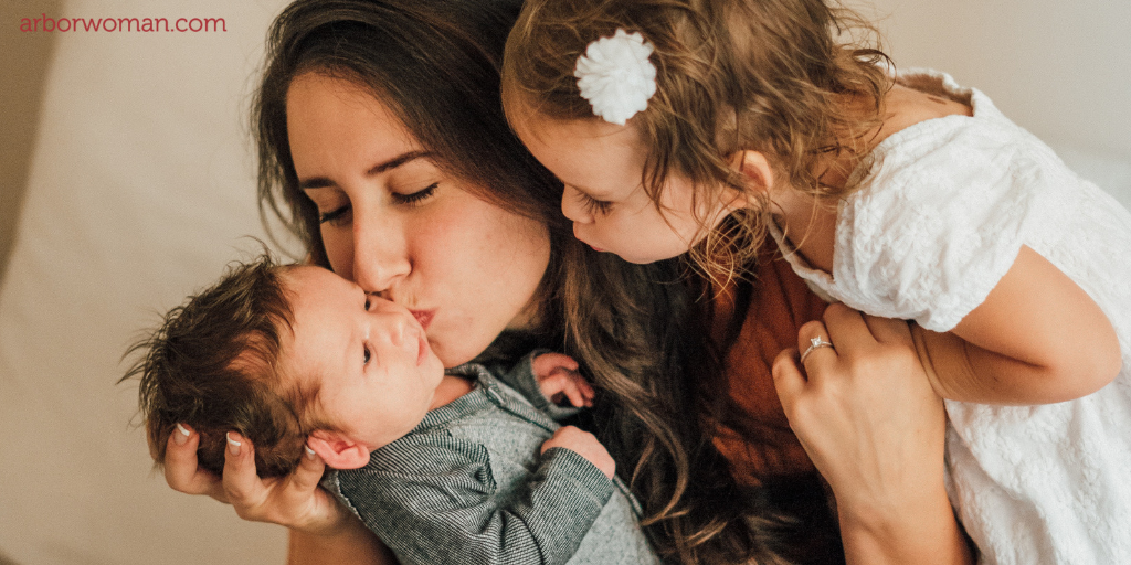 Mom and toddler kiss infant